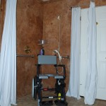 A shower chair, grab bar, hand-held shower sprayer, and shower curtains in a barrier-free design bathroom